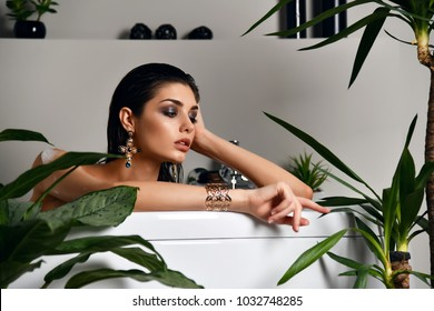 Young beautiful woman lying in bathtub and taking bath in eco bathroom with green plants