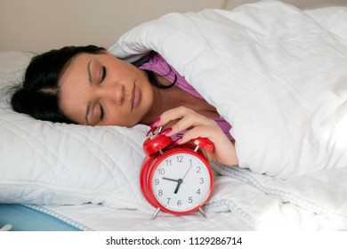 Young beautiful woman lying in bed suffering from alarm clock sound covering head and ears with pillow making unpleasant face. Early wake up, not getting enough sleep, going work concept