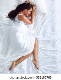 Young beautiful woman lying in bed at home