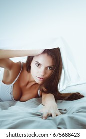 Young beautiful woman lying in bed under cover