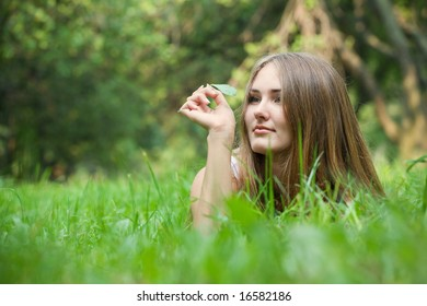Young beautiful woman lying at grass and looking at blade of grass in her hand