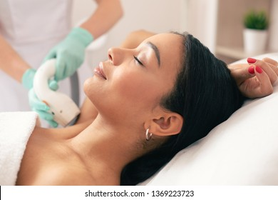 Young beautiful woman lying with her eyes closed and smiling while undergoing laser hair removal on her armpit