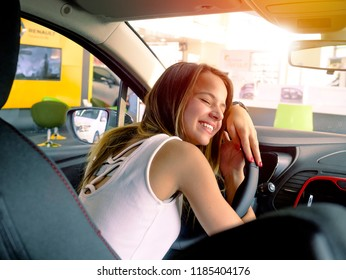 Young beautiful woman lying on an automobile rudder, closing eyes and hugging it. Happy client of car dealership after purchase of vehicle.