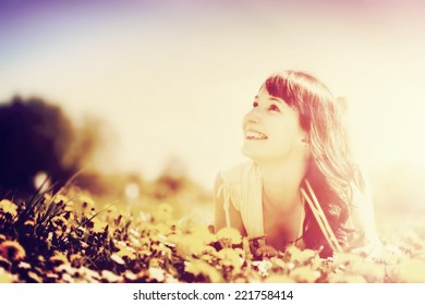 Young beautiful woman lying on grass full of spring flowers, looking happy at the sunny blue sky. Vintage, instagram style.