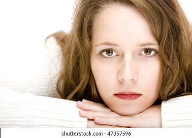 Young beautiful woman lying on floor and looks sad into camera.