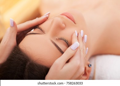Young beautiful woman lying on the bed with happy spa body and scrub skin at spa salon. concept of relaxing health aroma spa, treatment and body massage.