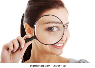 Young beautiful woman with magnifying glass.  Isolated on white.