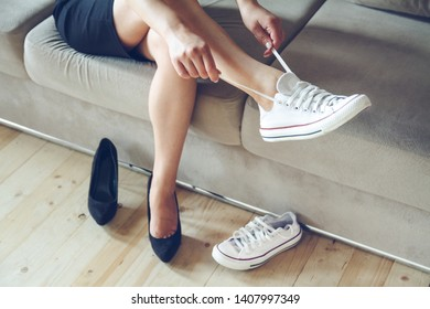 Young beautiful woman makes the choice between comfortable and uncomfortable shoes. Beautiful or comfortable shoes concept