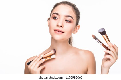 Young beautiful woman with makeup brushes near her face, skin care concept. Portrait of brunette girl on white background