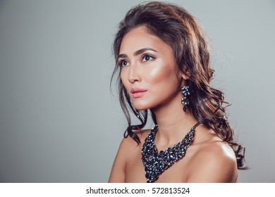 young beautiful woman with make-up in a chic necklace and earrings on a gray background.