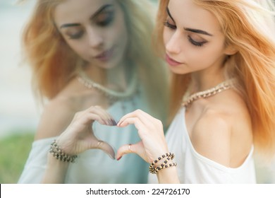 Young beautiful woman making a heart shape by hands in the mirror. Focus on hand.