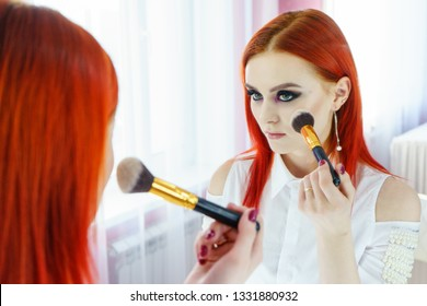 Young beautiful woman making make-up near mirror