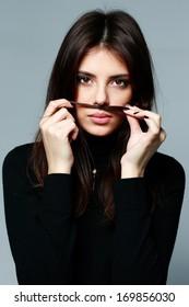 Young beautiful woman making mustache on gray background