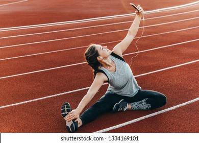 A young beautiful woman making selfie sitting at a stadium running track.