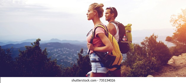 Young beautiful woman and man travelers are enjoying hike and beauty nature view during rest in the fresh air, two wanderers are taking break between walking in mountains during their summer adventure
