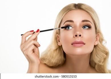 Young Beautiful Woman Mascara, making makeup, face close up portrait.