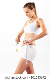 young beautiful woman measuring her abdomen with a meter-stick