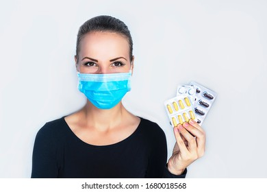 Young, beautiful woman in a medical mask, on a white background. The female is holding a blister with troche and pills. from the virus and looks directly at the camera. Epidemic, coronavirus, pandemic