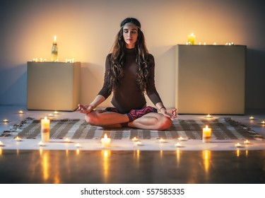 Young beautiful woman meditating on lotus pose in cozy room with candles. Padmasana