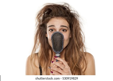 young beautiful woman with messy hair poses with hairbrush