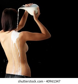 Young beautiful woman with milk, isolated on black. Skin care concept