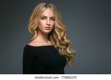 Young beautiful woman model with long beauty blonde curly hair portrait. Beautiful female girl with perfect healthy makeup and hairstyle