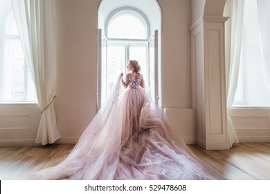 Young beautiful woman model in a stylish evening dress made of light tulle posing on a white room.