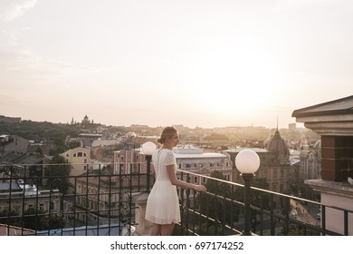 Young beautiful woman model in a stylish evening dress posing on a background of the city on the balcony of an old building.