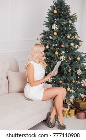 Young beautiful woman with modern digital tablet pc at home interior. Portrait of smiling blond happy businesswoman sitting on couch near Christmas tree. Vertical color photography.