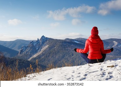 The young beautiful woman in mountains has a rest in the winter at the weekend, meditation, yoga
