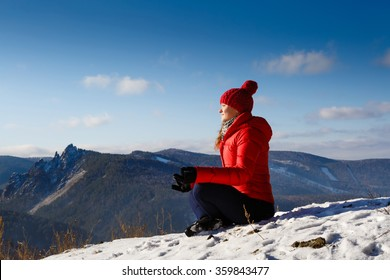 The young beautiful woman in mountains has a rest in the winter at the weekend, soft focus