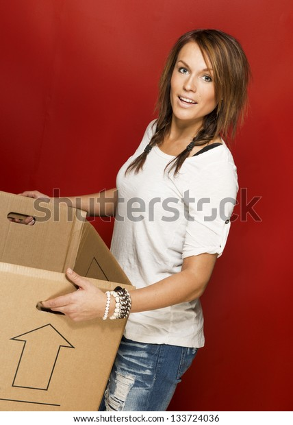 Young beautiful woman moving house and carrying box.