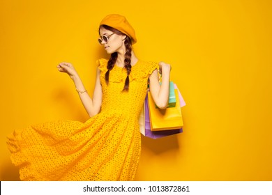 young beautiful woman with multi-colored packages, shopping, yellow background
