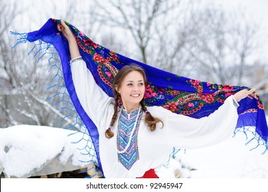 young beautiful woman in national ukraine suite at snowy winter