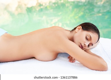 Young beautiful woman in nature lake health spa laying with eyes closed by calm water relaxing for massage, outdoors retreat. Healthy female leisure recreation wellbeing wellness beauty lifestyle.