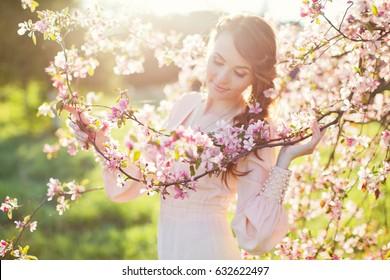 young beautiful woman near blooming tree