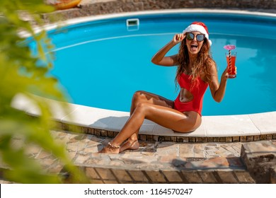 Young beautiful woman near the swimming pool in Santa Claus hat celebrating New Year and Christmas in hot country with glass of cocktail.