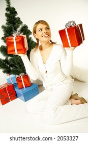 Young beautiful woman next to christmas tree and presents