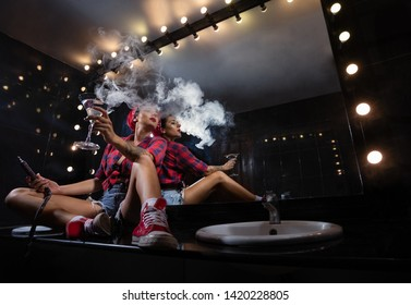 Young, beautiful woman in the night club in restroom smoke a hookah or shisha and drink martini. The pleasure of smoking. Sexy smoke with vape.
