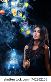Young, beautiful woman in the night club, bar smoke a hookah or shisha. The pleasure of smoking. Fruits in the smoke. Copy space. Hookah advertisement concept.
