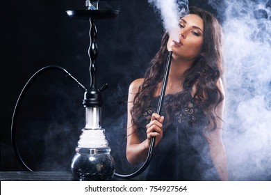 Young, beautiful woman in the night club or bar smoke a hookah or shisha. The pleasure of smoking. Sexy smoke with vape.