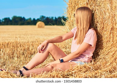Young beautiful woman on a background of haystacks field. Sexy blonde in a field with haystacks