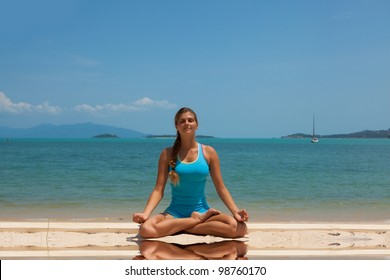 Young beautiful woman on the beach making yoga