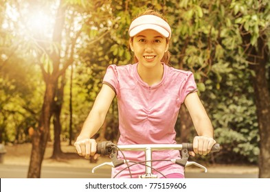 Young beautiful woman on bicycle at autumn park
