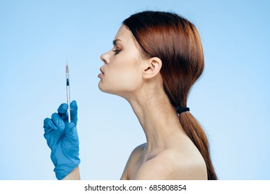 Young beautiful woman on a blue background in medical gloves holds a syringe, medicine, plastic.