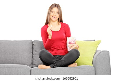Young beautiful woman on a sofa watching TV and eating popcorn isolated on white background