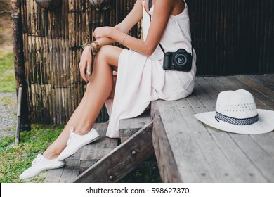 young beautiful woman on tropical vacation in asia, summer style, white boho dress, sneakers, digital photo camera, traveler, straw hat, legs close up details
