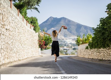 young beautiful woman on vacation jumping. In one hand sandals in the second hand hat.
