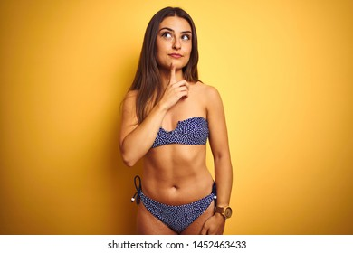 Young beautiful woman on vacation wearing bikini standing over isolated yellow background Thinking concentrated about doubt with finger on chin and looking up wondering