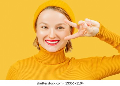 Young beautiful woman on yellow background smiling with happy face showing victory sign.